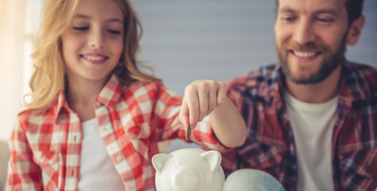 father and daughter putting coin in piggy bank